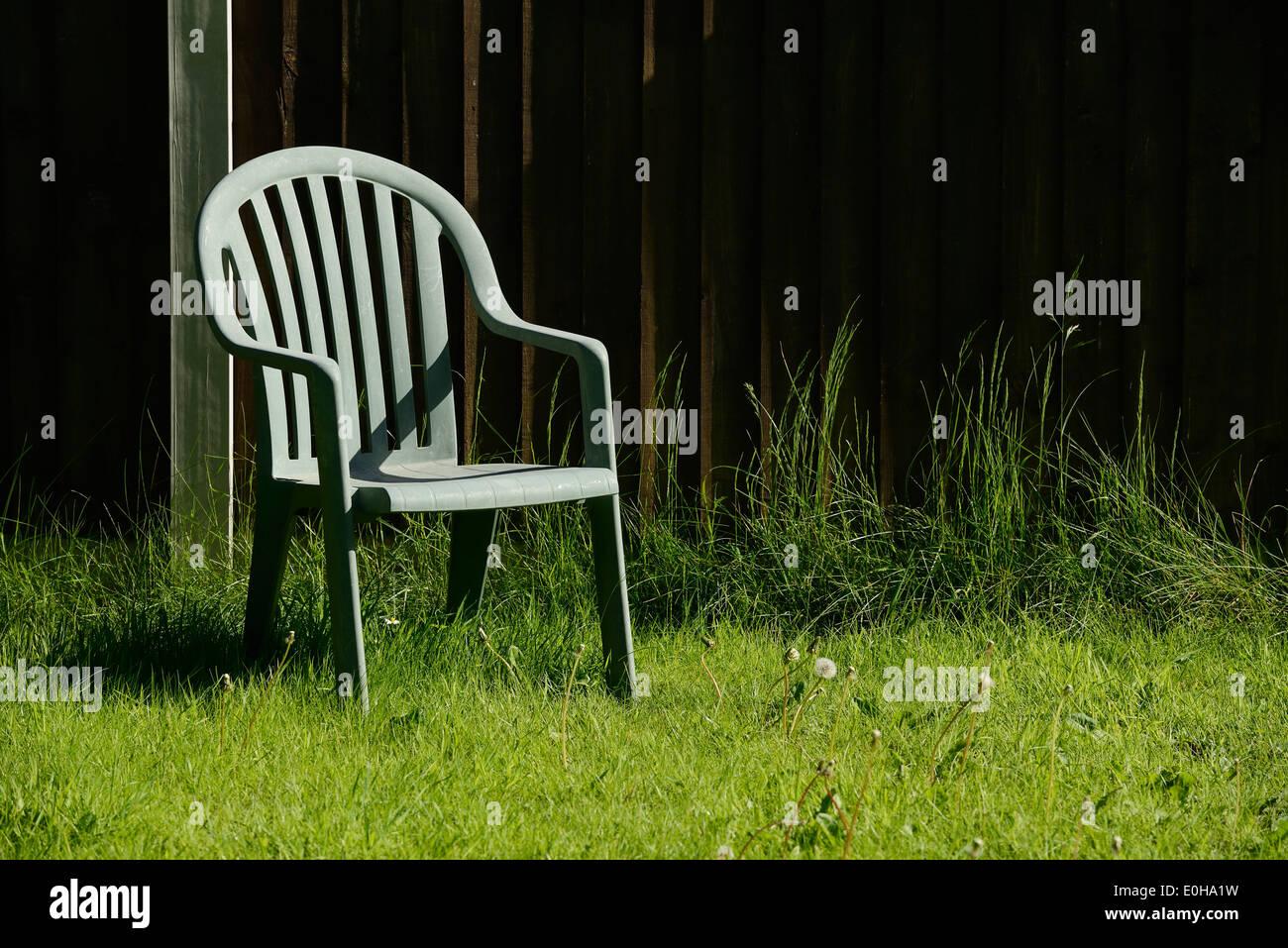 Solitary green plastic garden chair - Stock Image