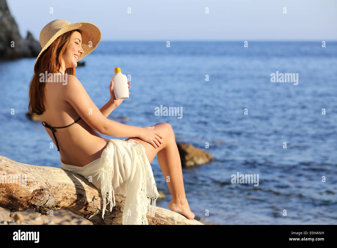 Woman on holidays on the beach applying sunscreen protection on leg with the horizon in the background - Stock Image