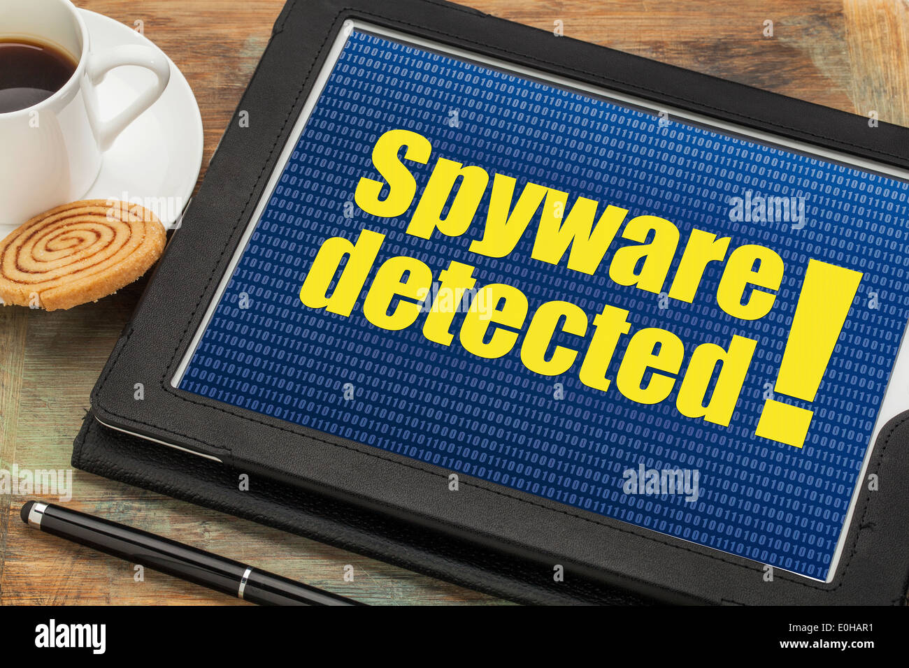 spyware detected alert on a digital tablet with a cup of coffee - Stock Image