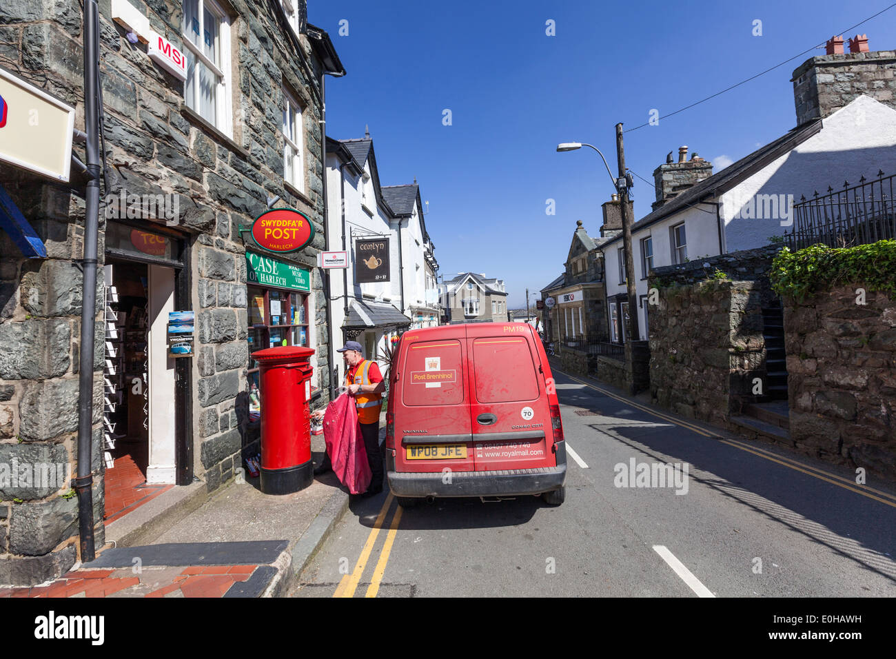 Postman recollecting letters in a post box in Stryd Fawr view, Harlech, - Stock Image