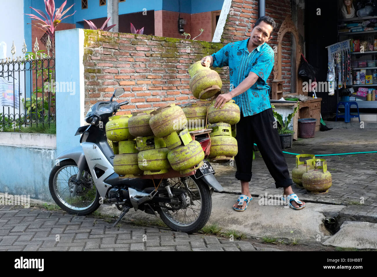 seller delivers propane gas bottles to a village shop for resale from his heavily laden motorbike in rural village Stock Photo
