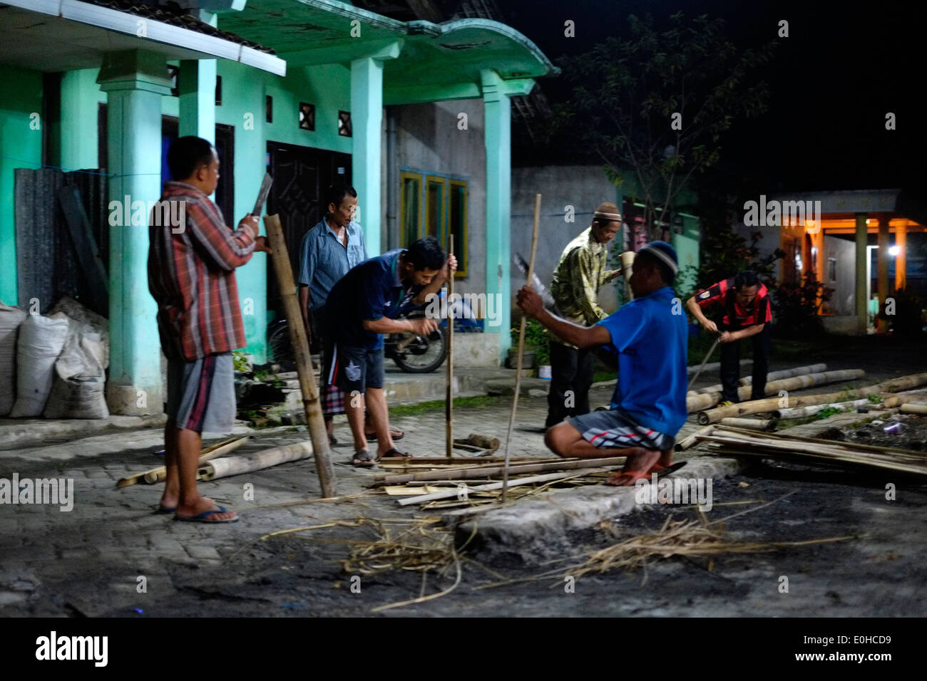 indonesian local villagers working at night by the light of a single strip lamp fashioning bamboo and discarding the waste wood - Stock Image