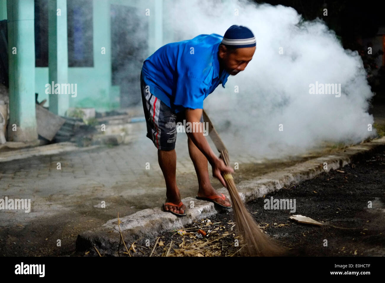 indonesian local villager working at night by the light of a single strip lamp fashioning bamboo and discarding the waste wood - Stock Image