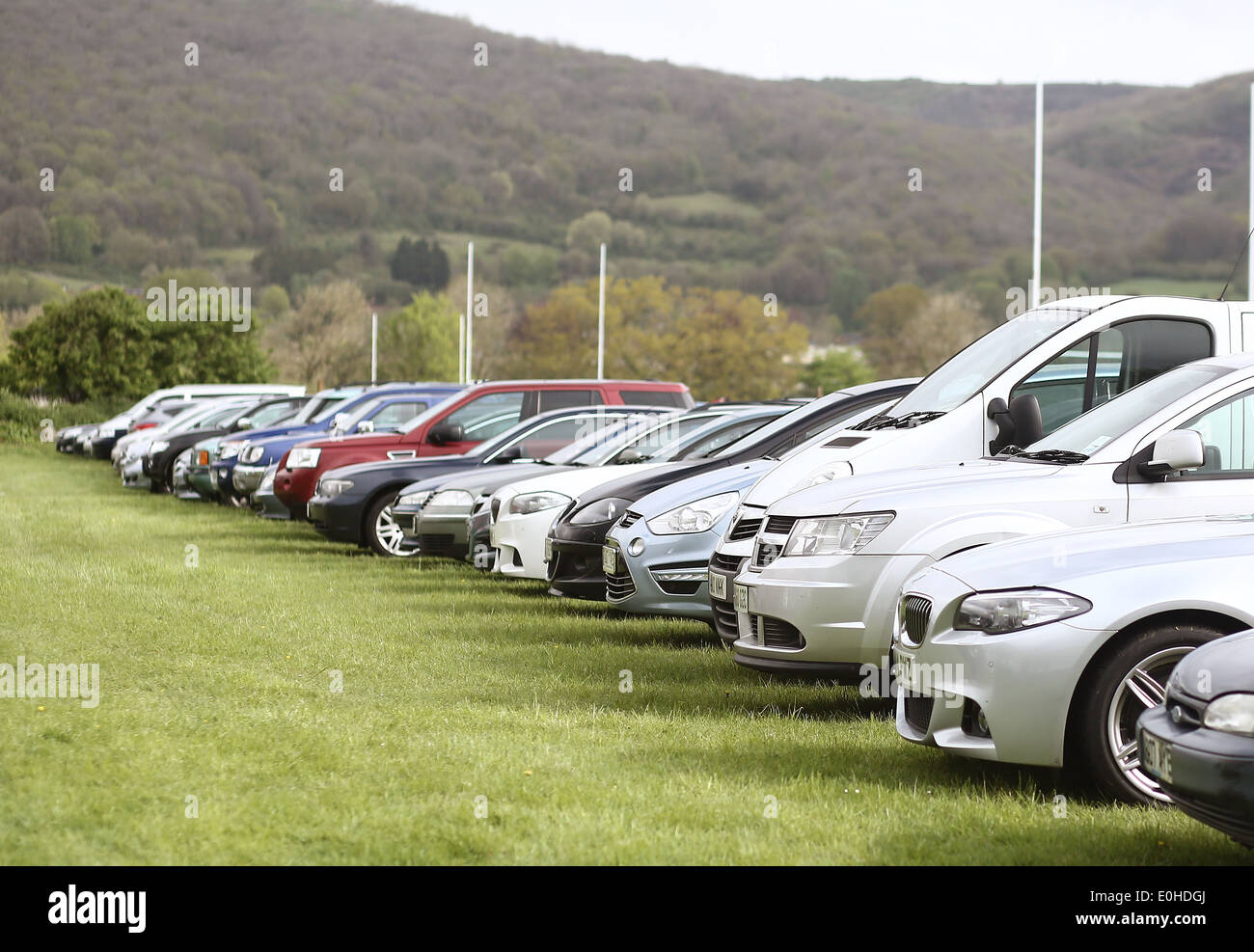 Lines of parked cars, SUV's and minivans on a grass field used as a parking lot for a sports event in Cheddar, 27 April 2014 - Stock Image