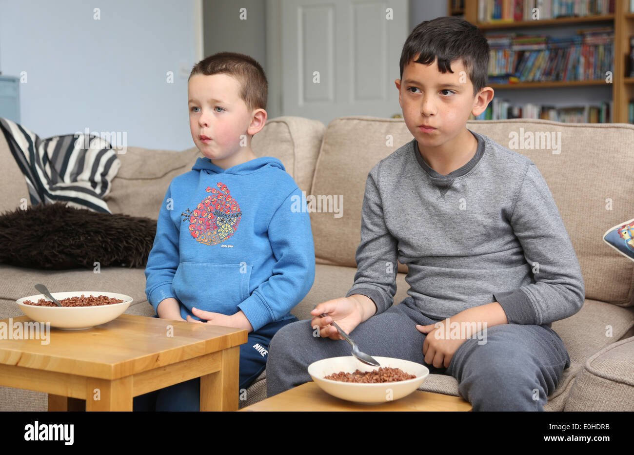 Children eating breakfast in font of the TV - Stock Image