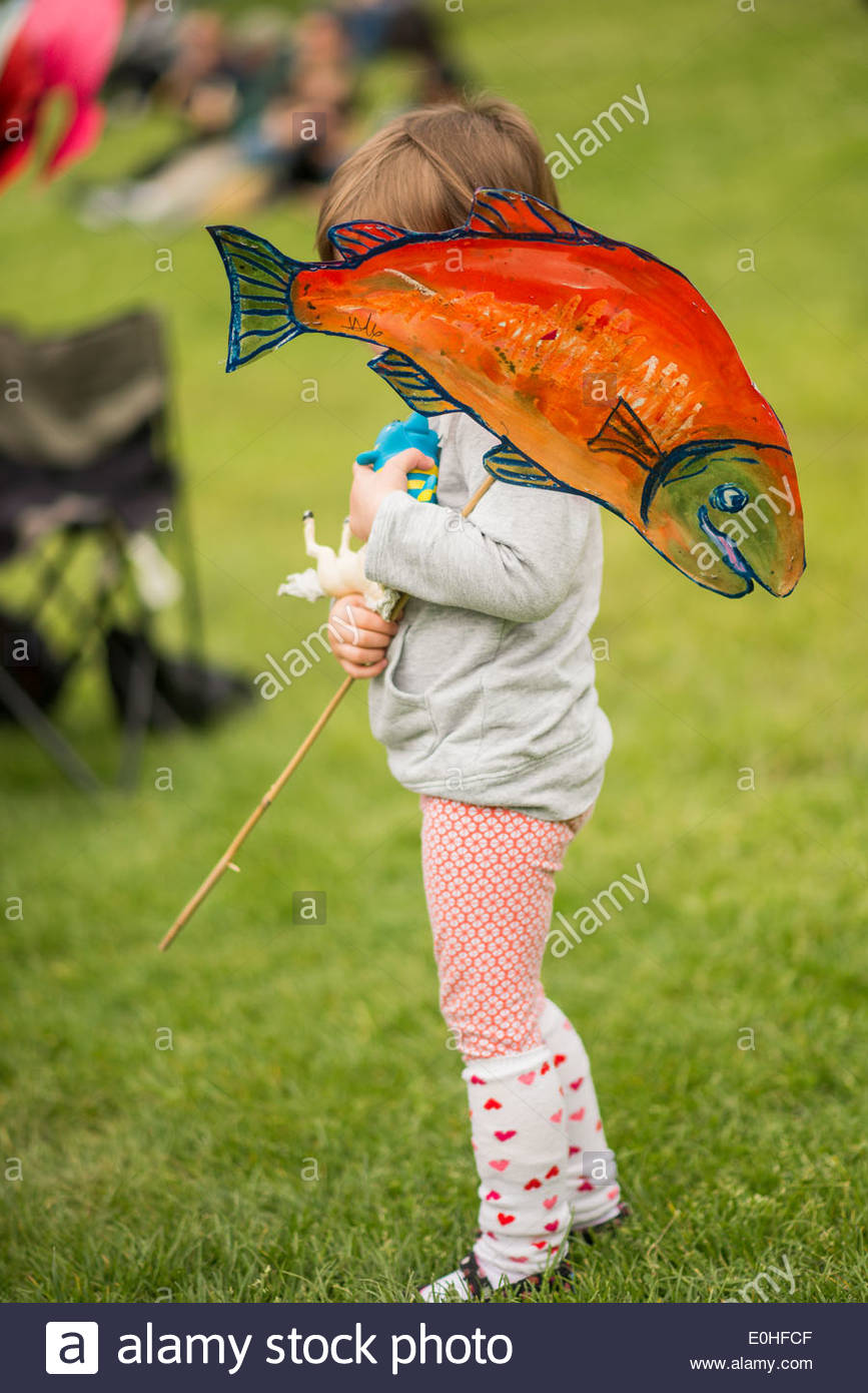 young protester with painted salmon prop, at the No Enbridge Pipeline Rally - Stock Image