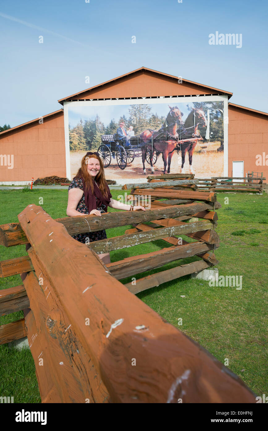 Young woman at Hobby Farm fence, Coombs, British Columbia, Canada - Stock Image