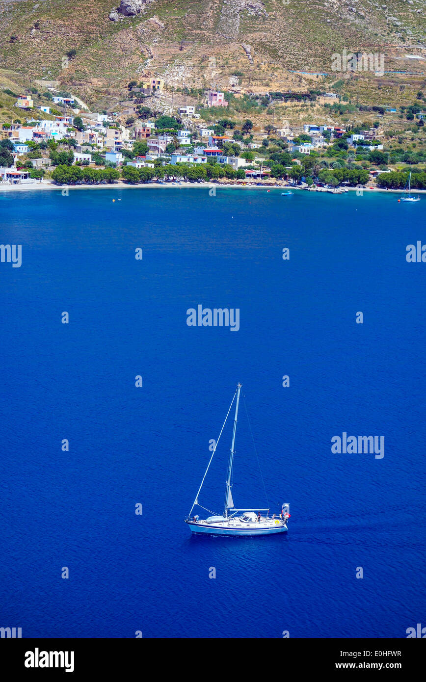 White yacht on blue sea, bay with surrounding hills, Greece - Stock Image
