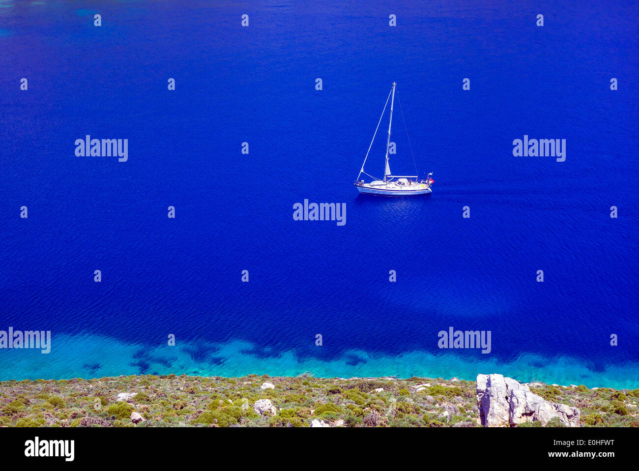 White yacht on blue sea, bay with surrounding hills, Greece Stock Photo