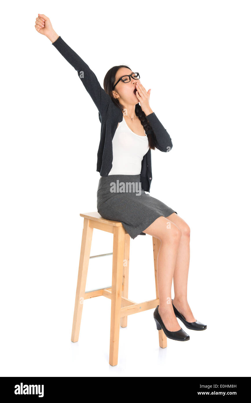 Full body Asian business woman yawning, seated on chair isolated white background. - Stock Image