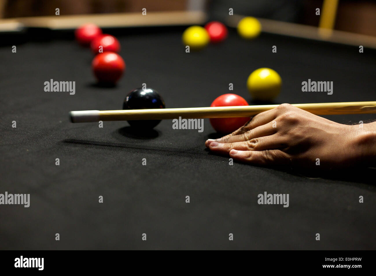 close up of hand and cue on pool table - Stock Image