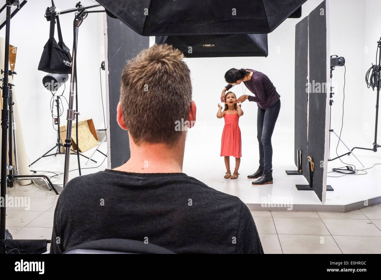 Young female child on a set during a photoshoot for a fashion company The stylist is adjusting the clothes and hair - Stock Image