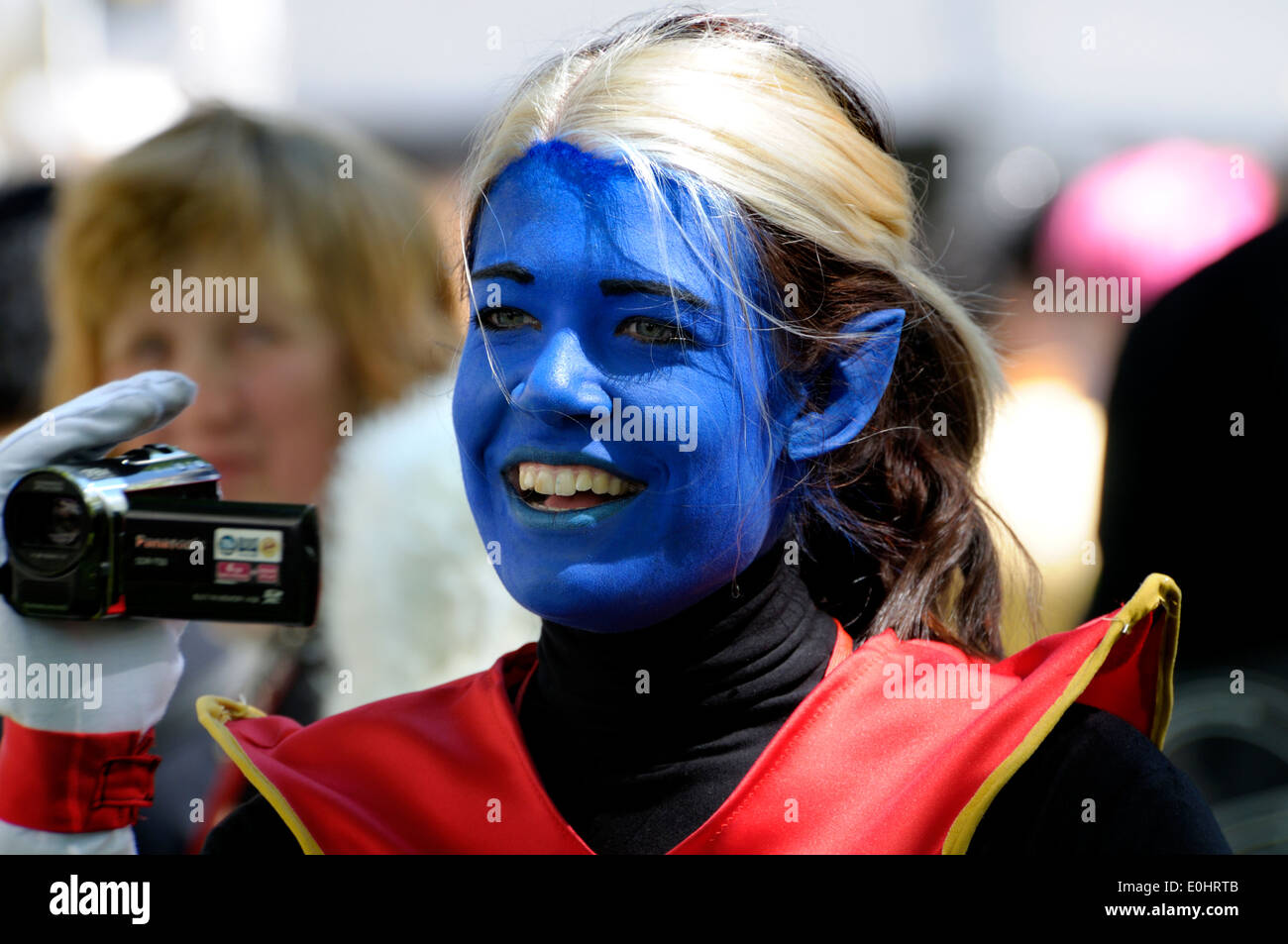 X-Men cosplay event in Leicester Square, London, 2104. Woman in costume with camcorder - Stock Image