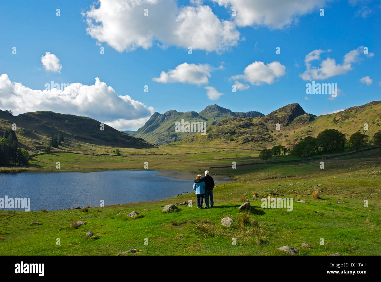 Couple looking beyond Blea Tarn to the Langdale Pikes, Little Langdale, Lake District National Park, Cumbria, England UK Stock Photo