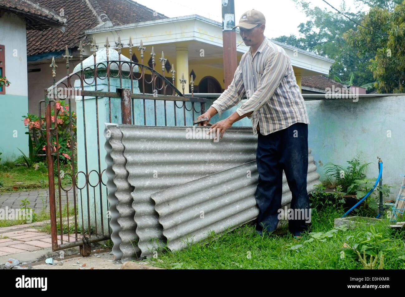 local worker handling asbestos sheets still in common use during construction in indonesia - Stock Image
