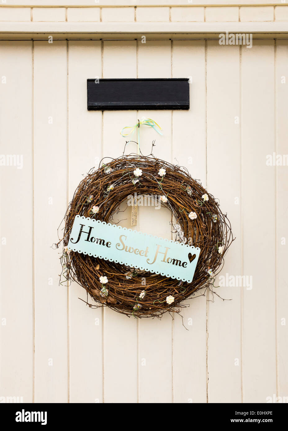 A 'Home Sweet Home' sign/wreath hangs on an English door in the village of Dunster, Devon, England - Stock Image