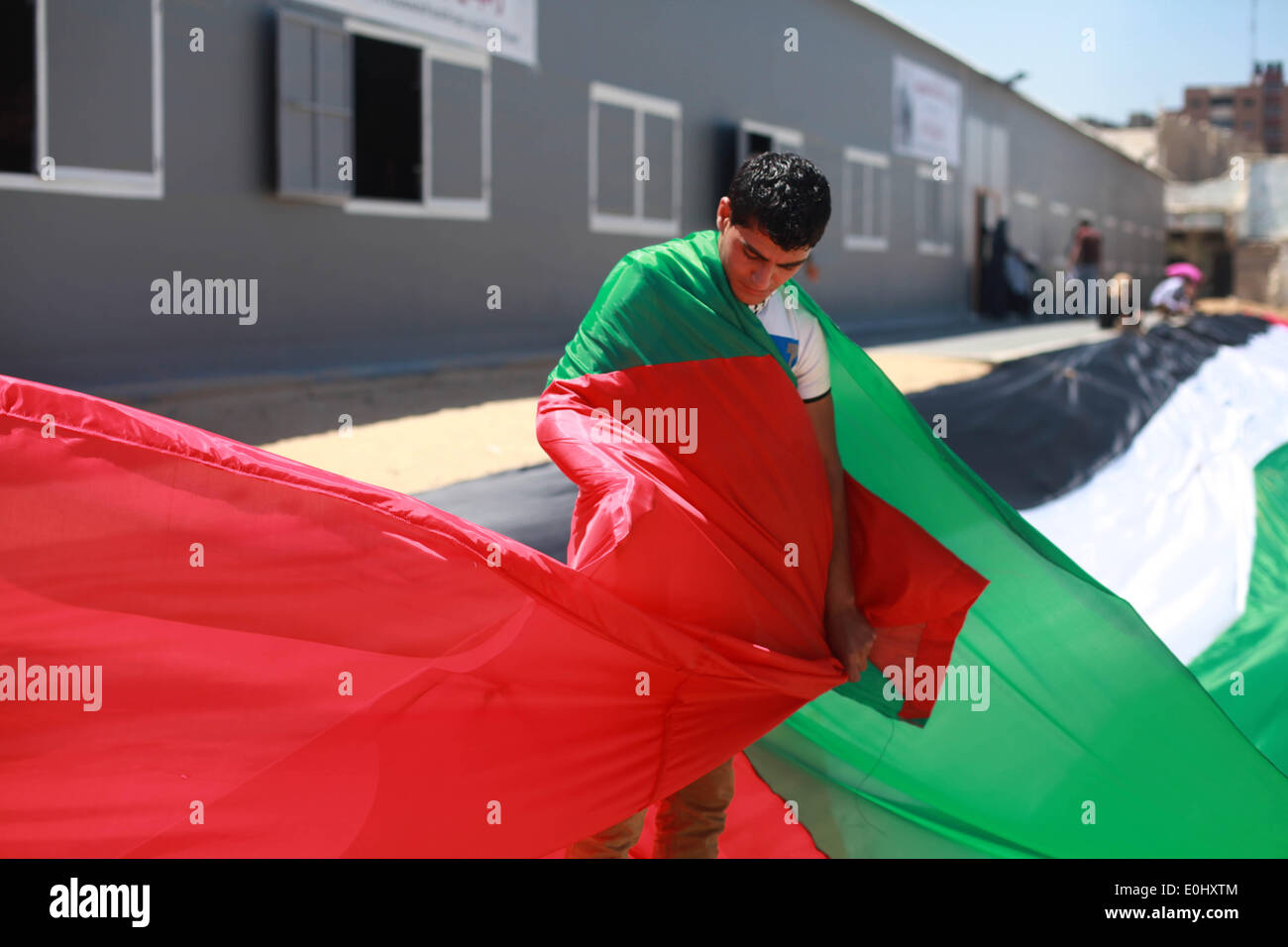 Gaza, Palestinian Territories. 14th May, 2014. Palestinians hold a large Palestinian flag during a rally ahead of Stock Photo