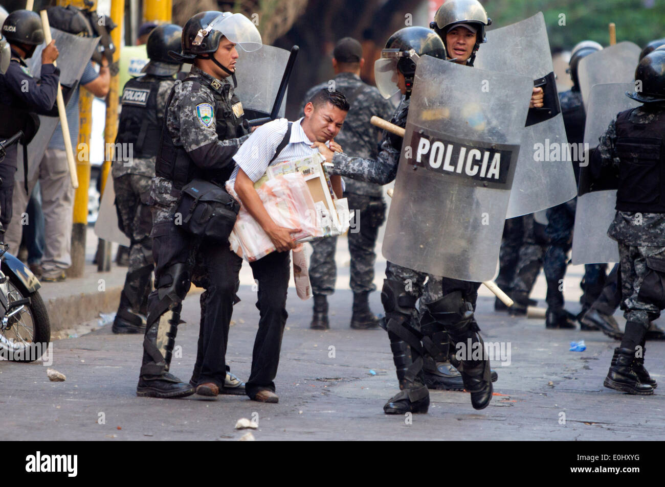 Tegucigalpa, Honduras. 13th May, 2014. Police elements detain a person during a clash between followers of the former Honduran President, Manuel Zelaya, and police, in front of the National Congress in Tegucigalpa, Honduras, on May 13, 2014. Followers and deputies of the Liberty and Refoundation Party (Libre, for its acronym in Spanish), the second political force in Honduras, broke in the National Congress on Tuesday, after clashing with police elements that guarded the Legislative Palace. Credit:  Rafael Ochoa/Xinhua/Alamy Live News Stock Photo