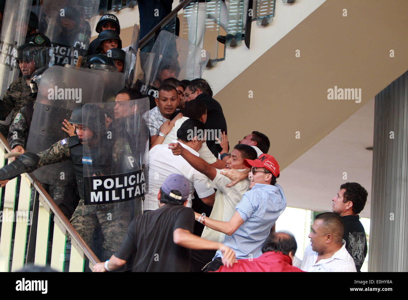 Tegucigalpa, Honduras. 13th May, 2014. Police elements and supporters of the former Honduran President Manuel Zelaya clash in front of the National Congress in Tegucigalpa, Honduras, on May 13, 2014. Followers and deputies of the Liberty and Refoundation Party (Libre, for its acronym in Spanish), the second political force in Honduras, broke in the National Congress on Tuesday, after clashing with police elements that guarded the Legislative Palace. Credit:  Rafael Ochoa/Xinhua/Alamy Live News Stock Photo