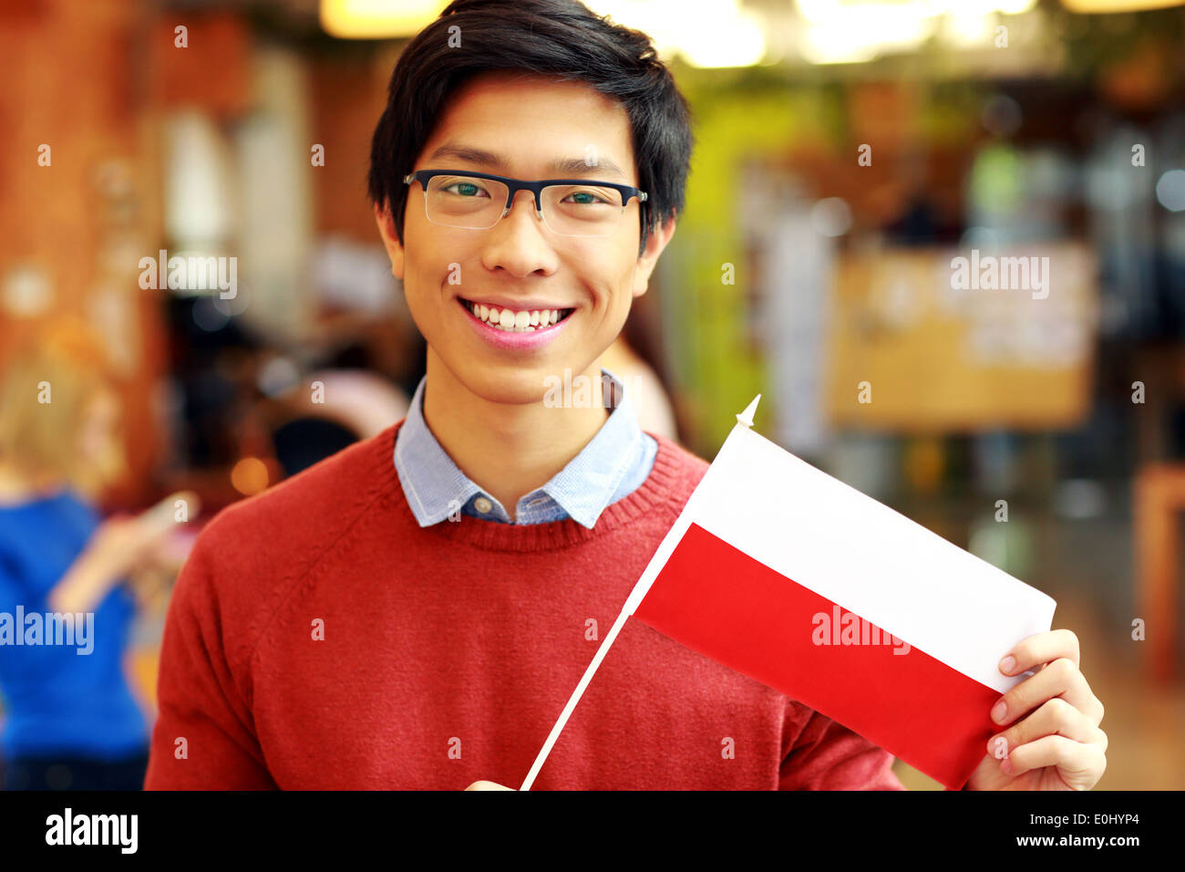 Smiling asian boy in glasses holding flag of Poland - Stock Image