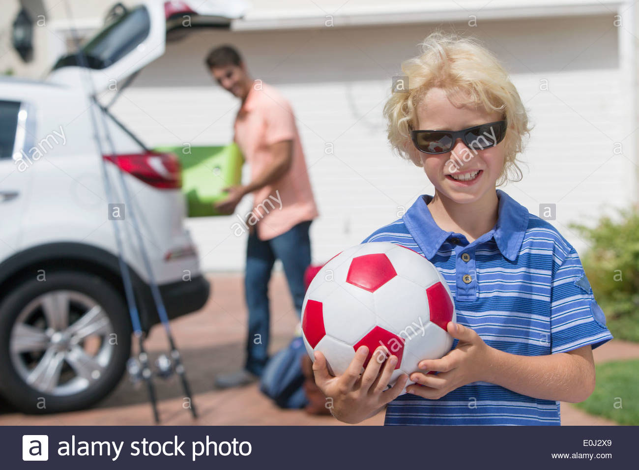 Portrait of smiling boy holding soccer ball in sunny driveway - Stock Image