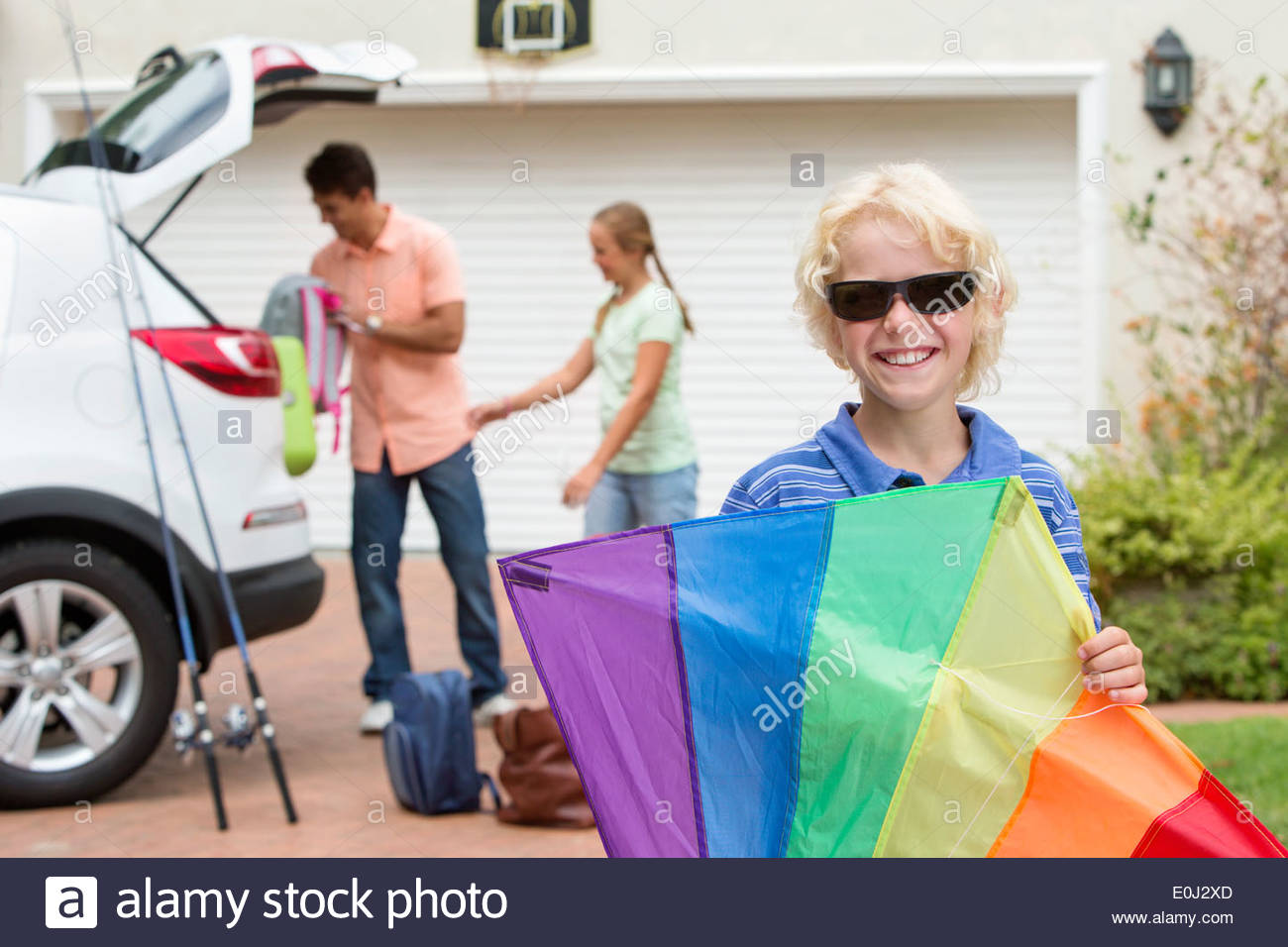 Portrait of smiling boy holding multicolor kite in driveway Stock Photo