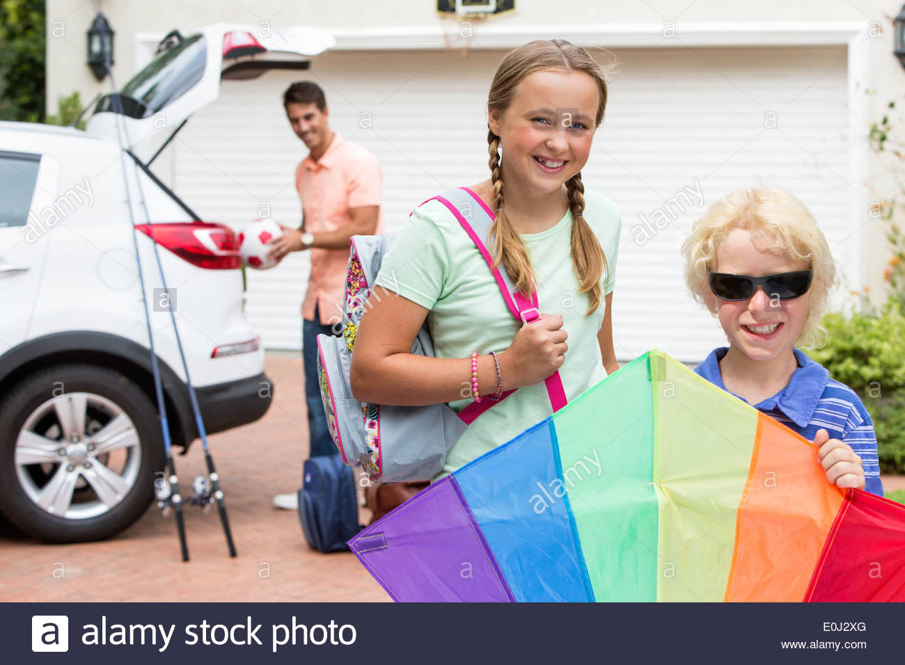 Portrait of brother and sister with multicolor kite in driveway - Stock Image