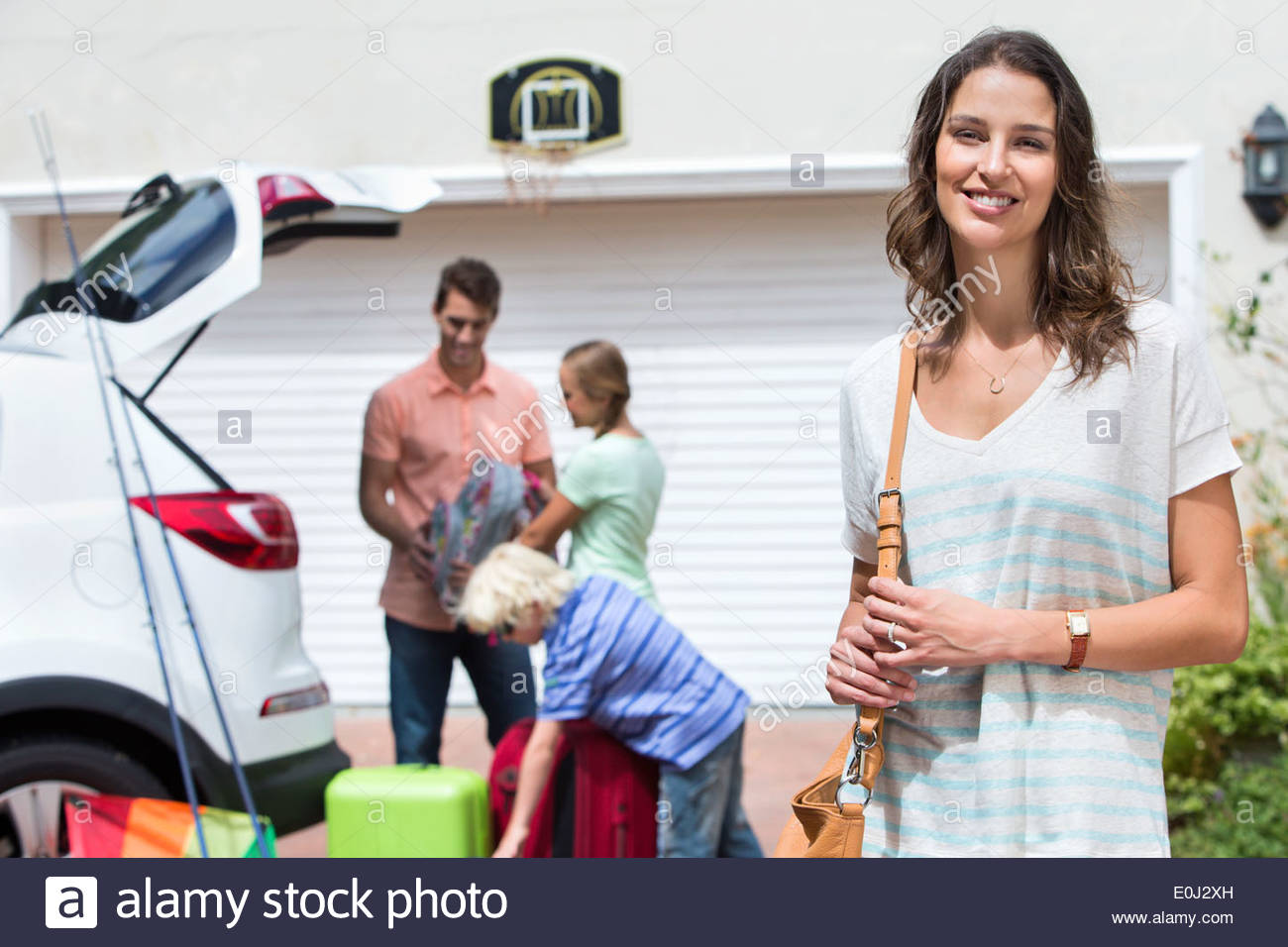 Portrait of smiling woman in driveway with family packing car in background - Stock Image