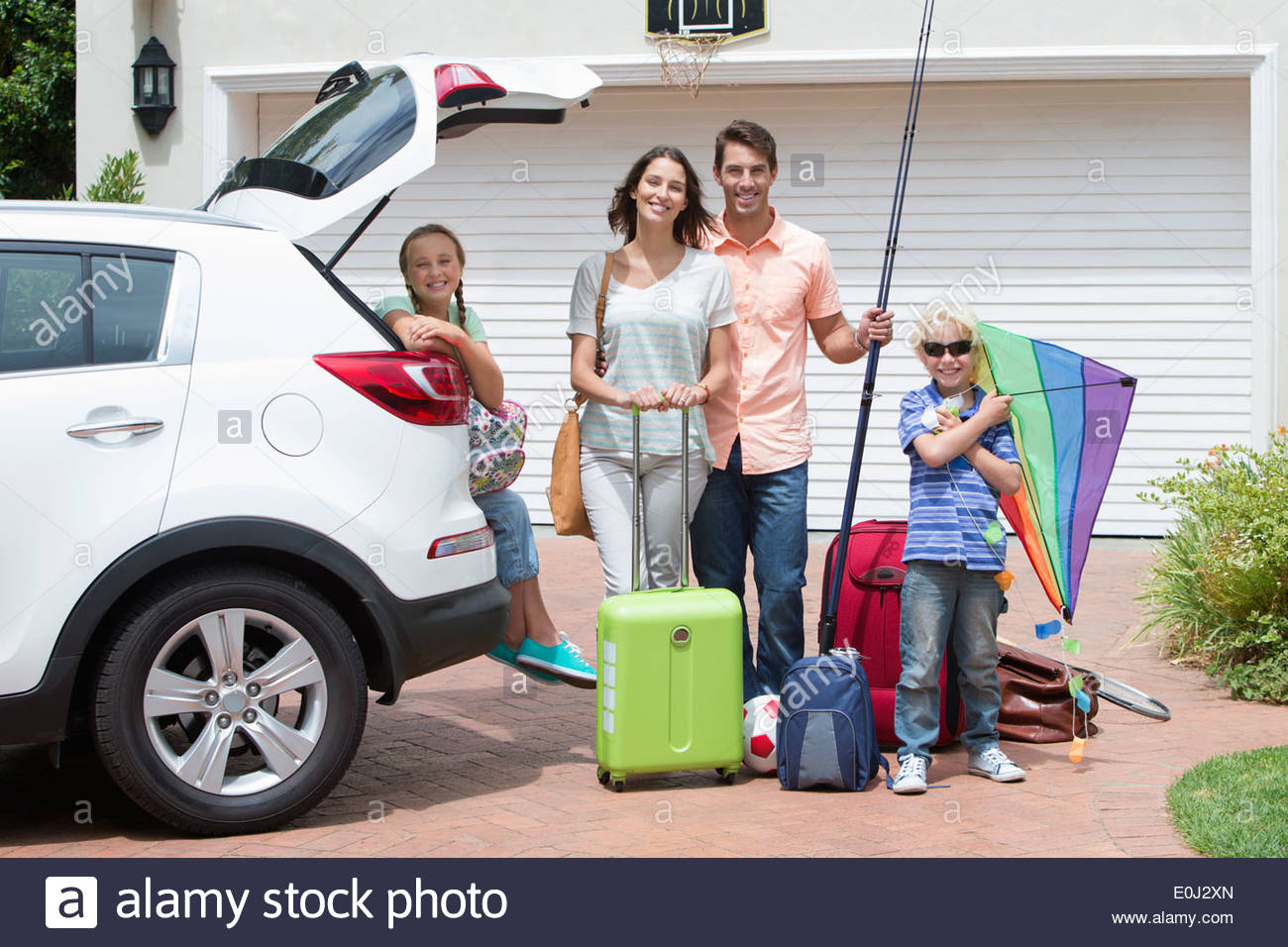 Portrait of smiling family packing car in sunny driveway - Stock Image