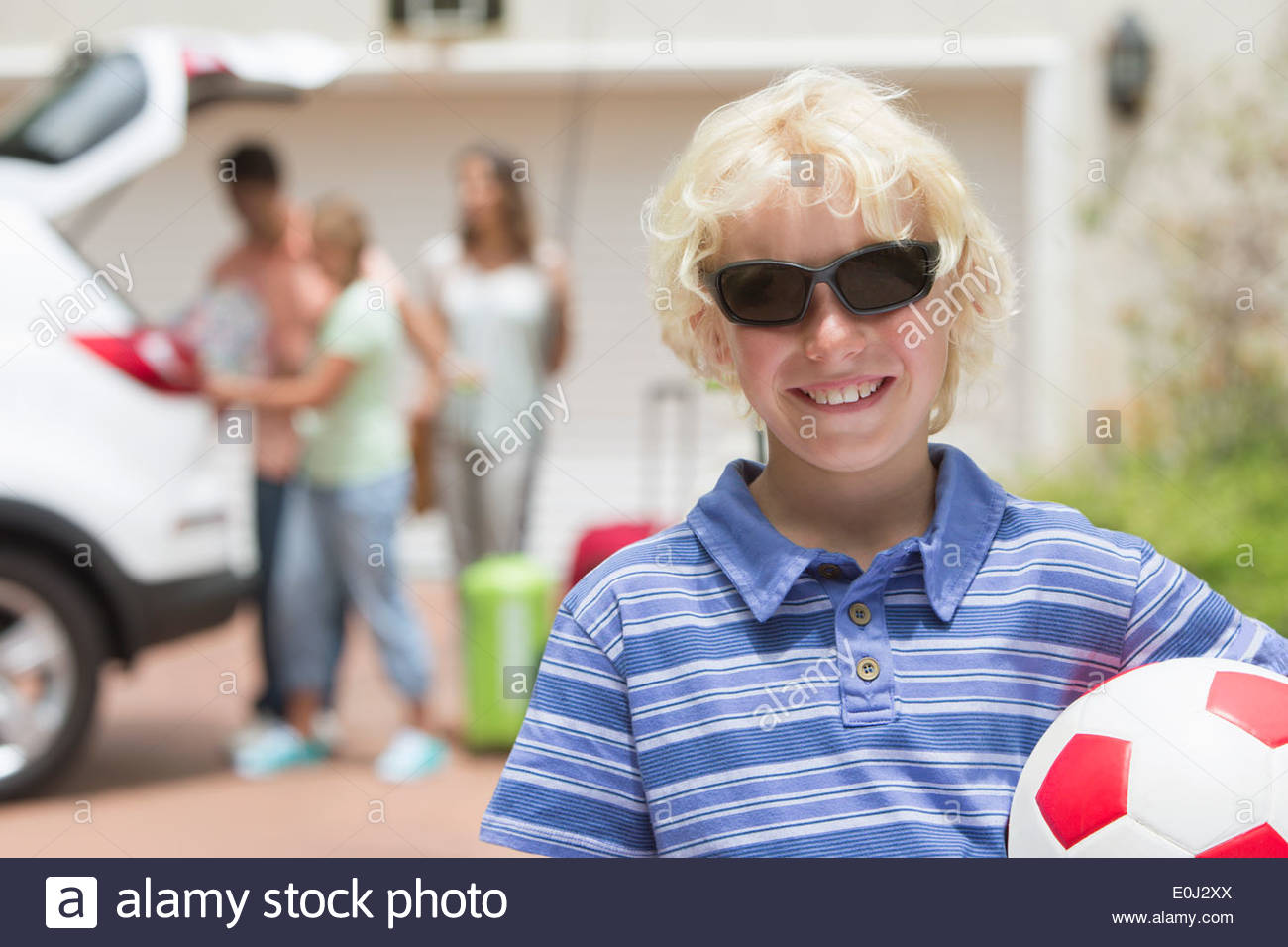 Portrait of smiling boy in sunglasses holding soccer ball in sunny driveway - Stock Image