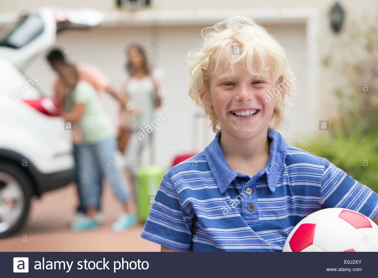 Portrait of smiling boy holding soccer ball in driveway - Stock Image