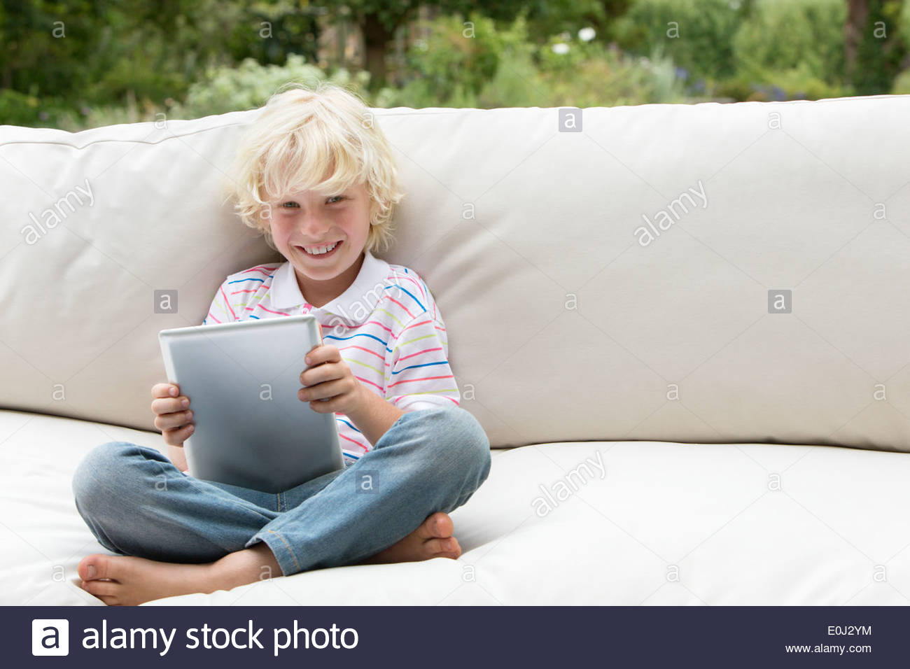 Portrait of smiling boy using digital tablet on outdoor sofa - Stock Image