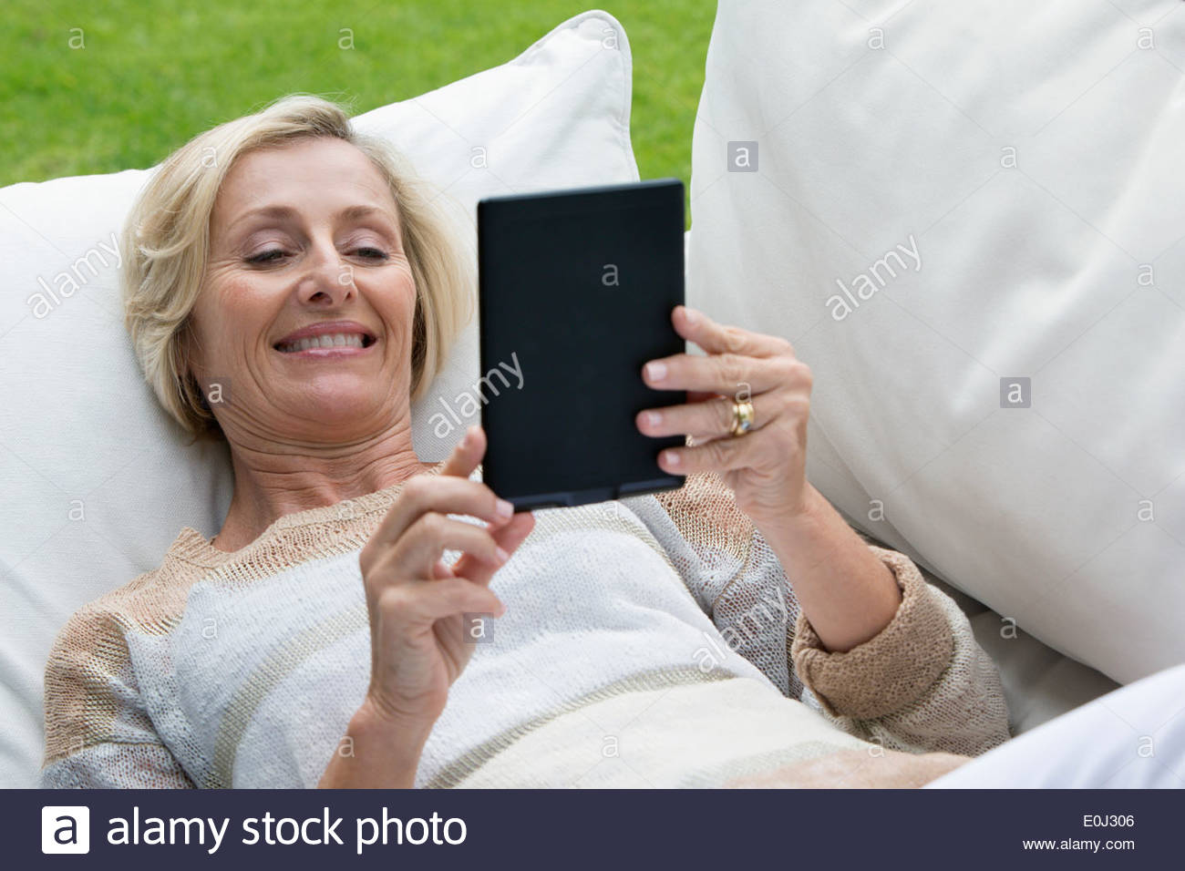 Senior woman laying on outdoor sofa and using digital tablet - Stock Image
