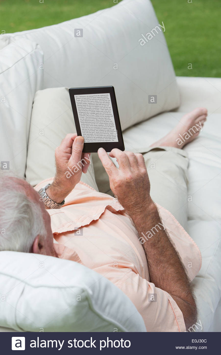 Senior man laying on outdoor sofa and using digital tablet - Stock Image