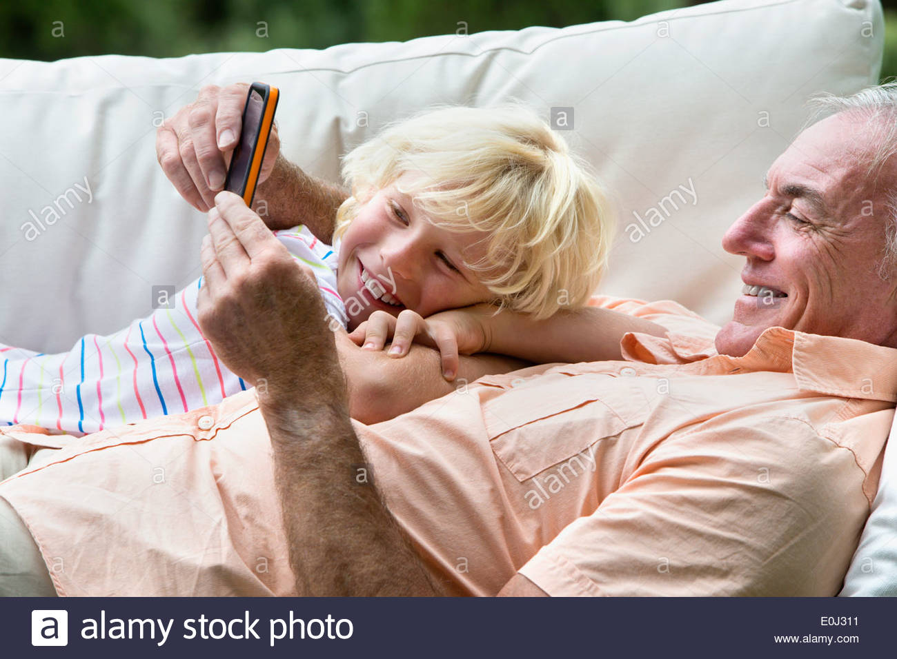 Smiling grandfather and grandson laying on outdoor sofa with digital tablet - Stock Image
