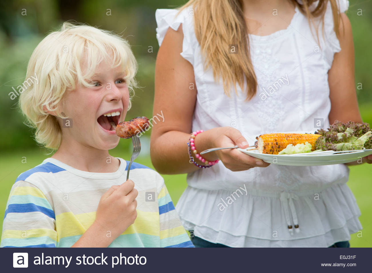 Close up of enthusiastic boy taking a bite of barbecued sausage - Stock Image