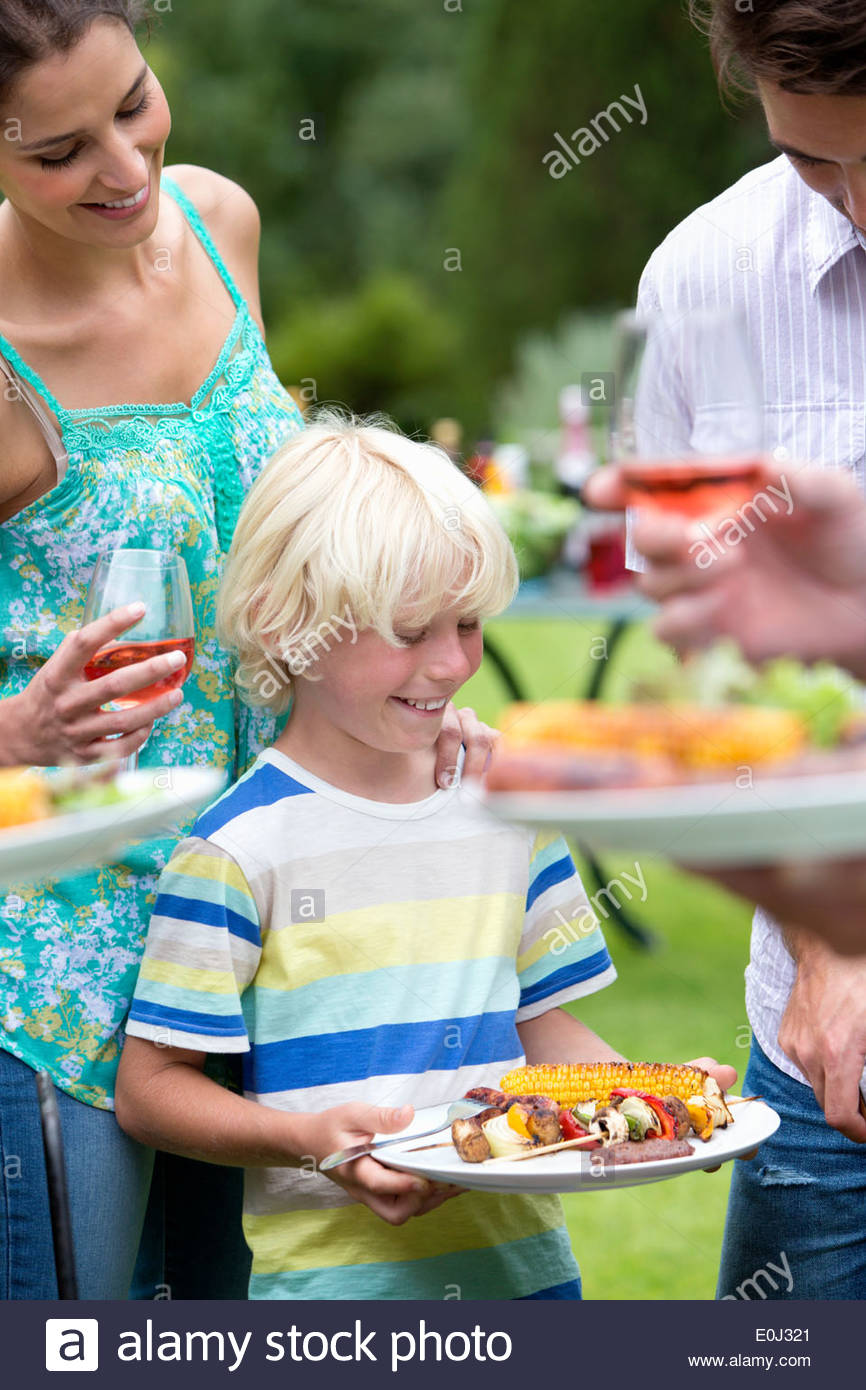 Happy family holding plates of barbecue - Stock Image