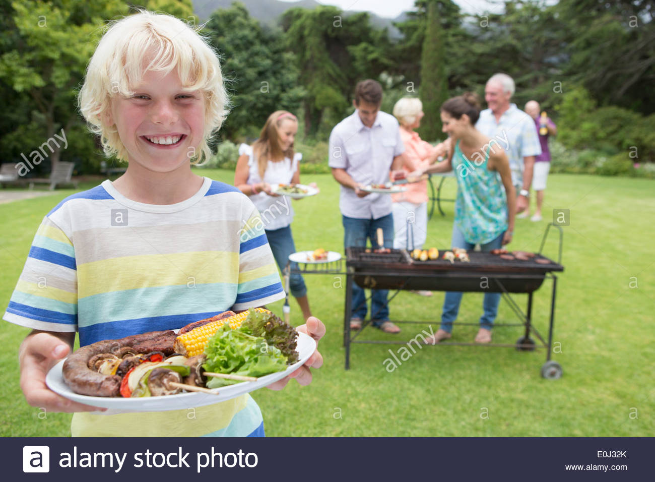 Portrait of smiling boy holding plate of barbecue with family in background - Stock Image