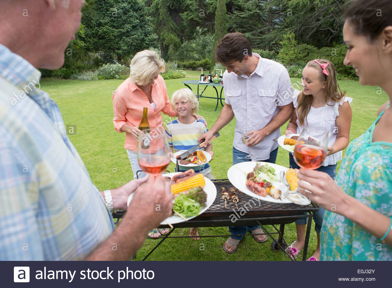 Multi-generation family serving barbecue - Stock Image