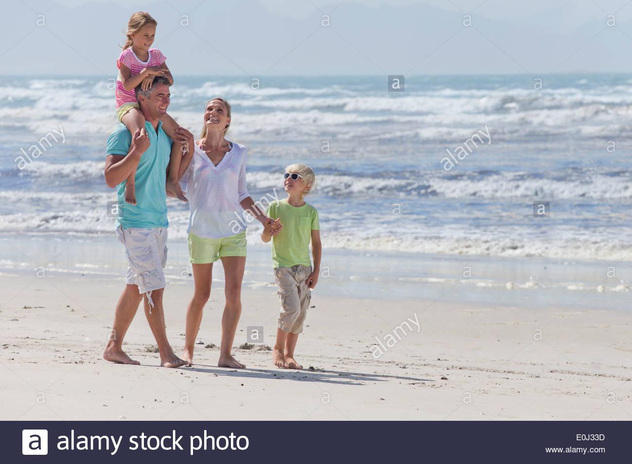 Family walking on sunny beach - Stock Image