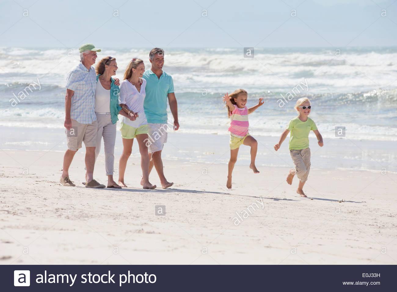 Multi-generation family walking on sunny beach Stock Photo