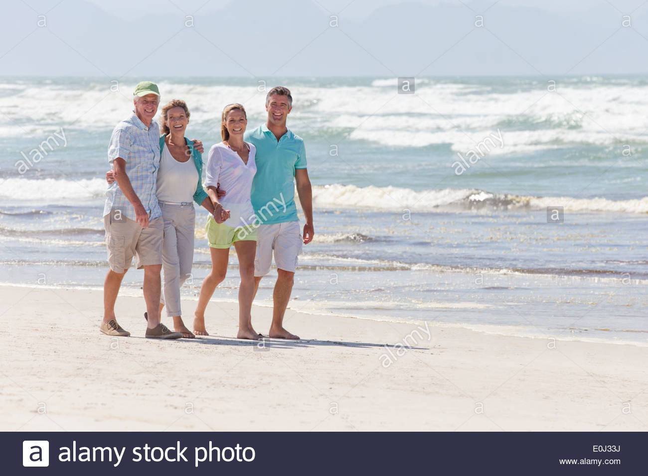 Portrait of happy couples walking on sunny beach - Stock Image
