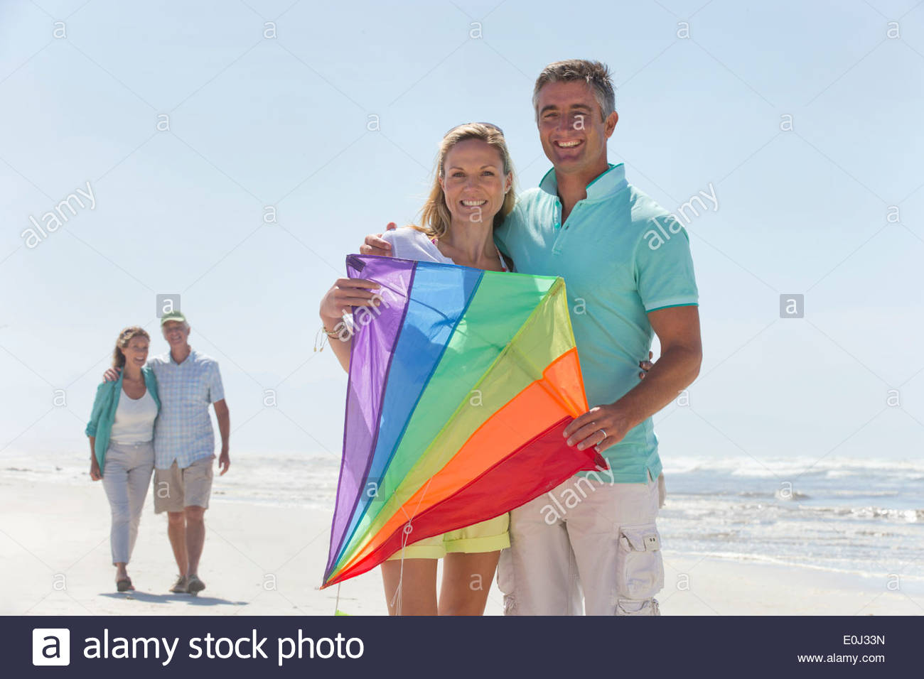 Portrait of smiling couple with kite on sunny beach - Stock Image