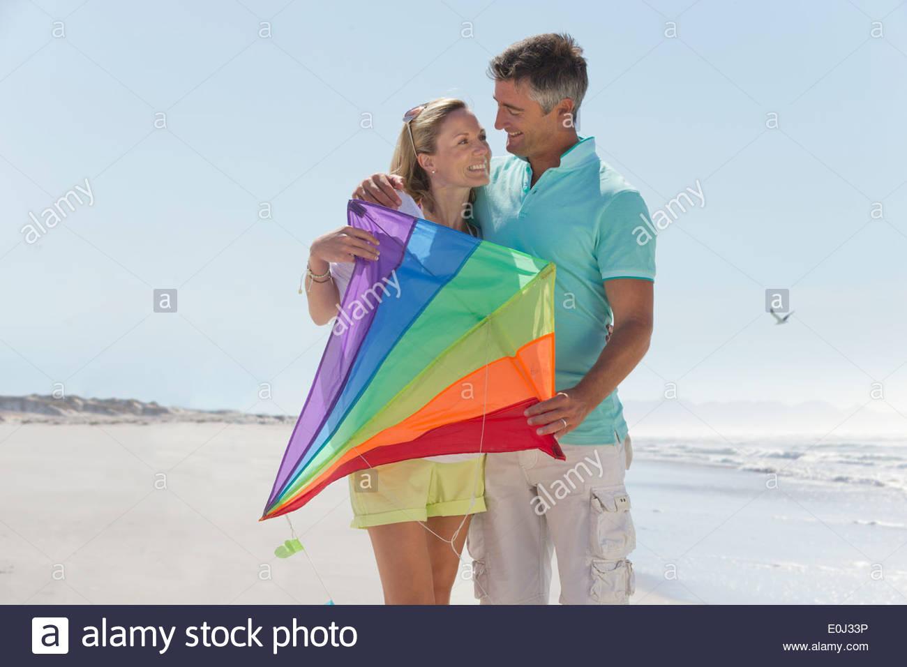Happy couple holding kite on sunny beach - Stock Image
