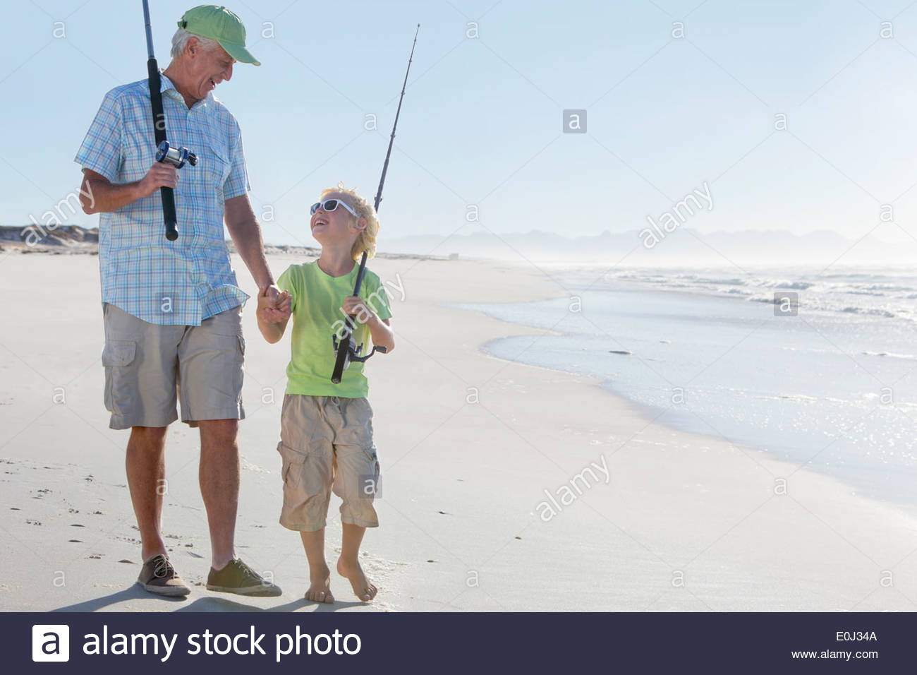 Grandfather and grandson with fishing rods on sunny beach - Stock Image