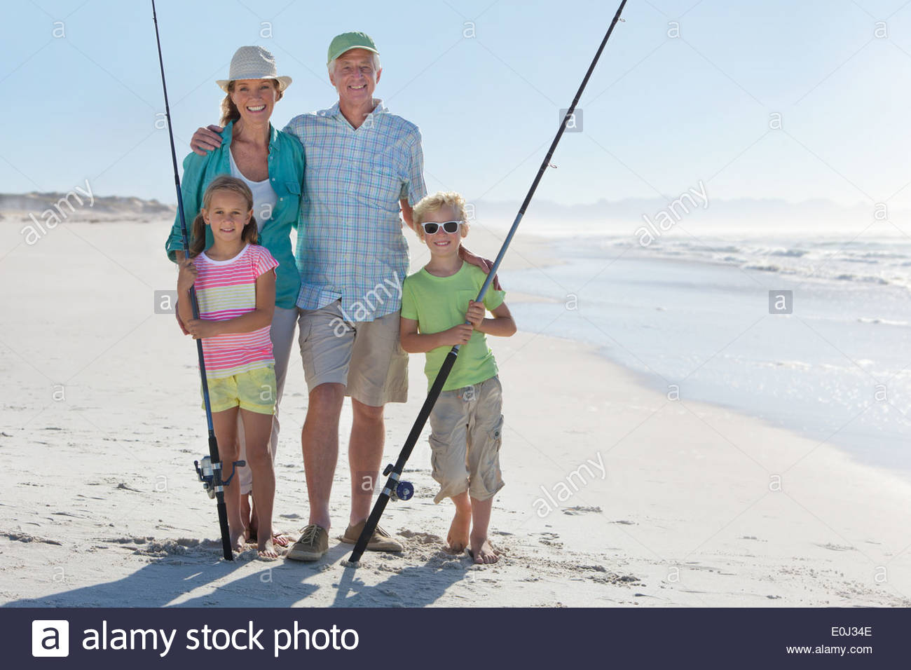 Grandparents and grandchildren with fishing rods on sunny beach - Stock Image
