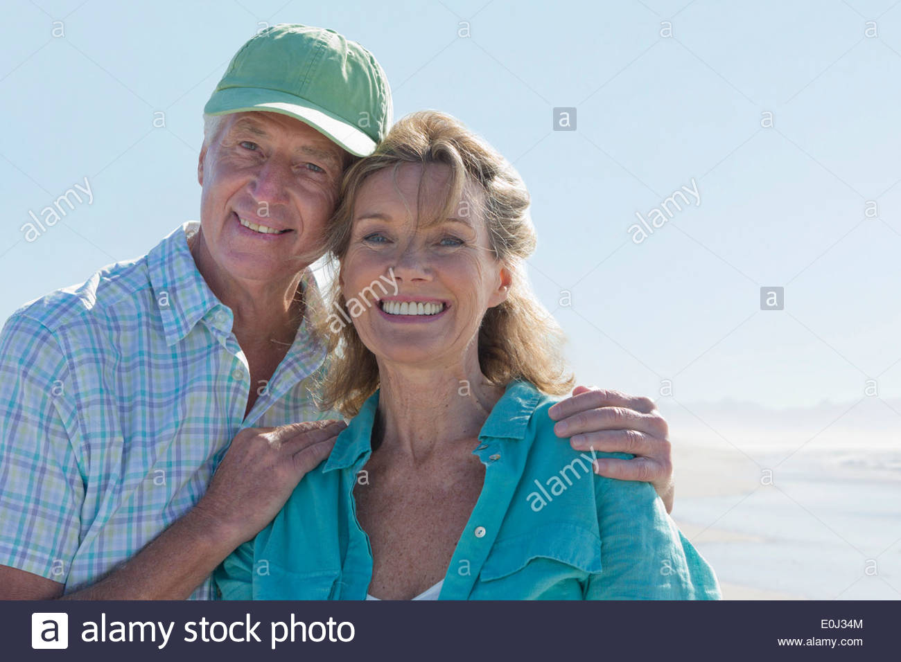 Close up portrait of smiling senior couple on sunny beach - Stock Image