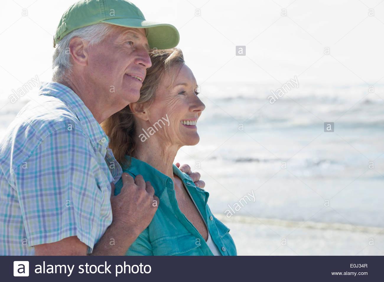Happy senior couple on sunny beach - Stock Image