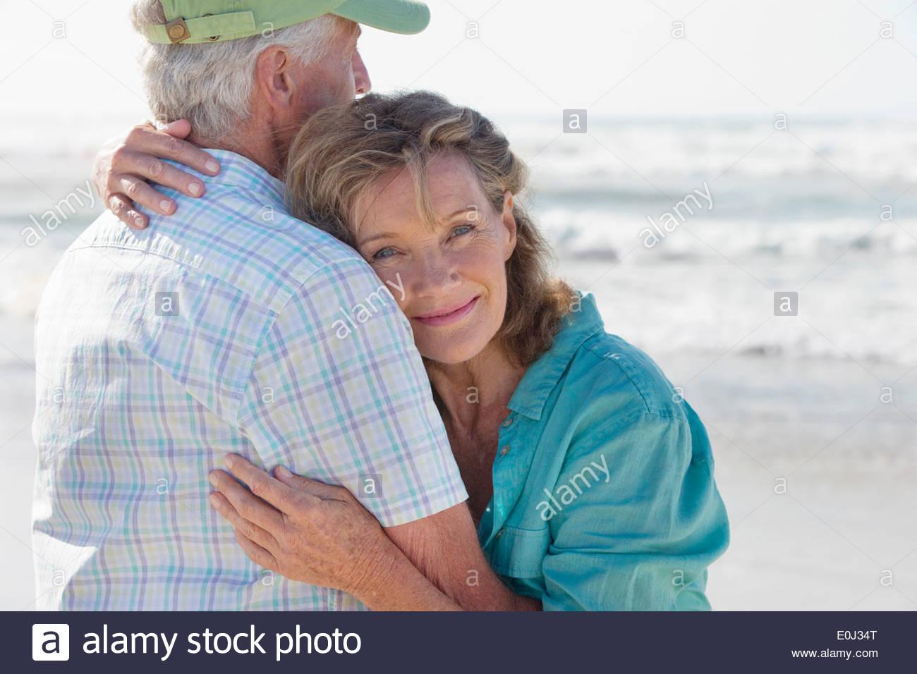 Happy senior couple hugging on sunny beach - Stock Image