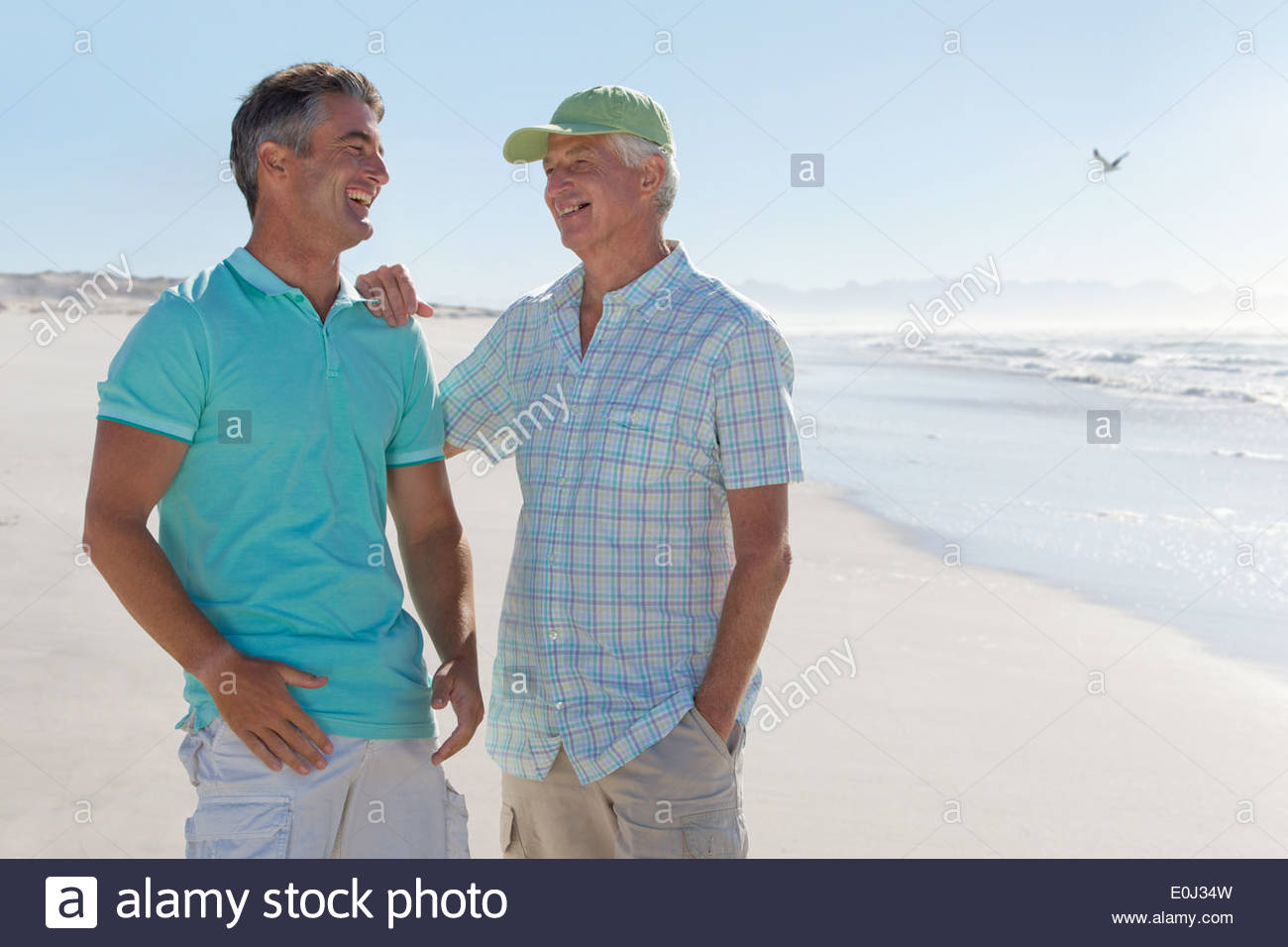 Happy father and son laughing on sunny beach - Stock Image